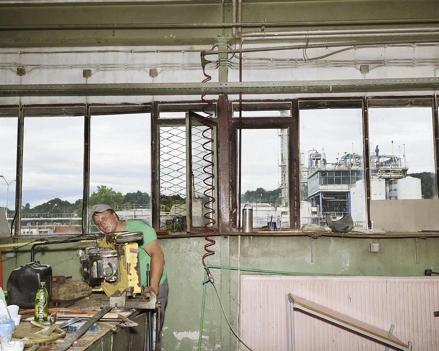 A worker repairs equipment in an engineering workshop at DITA. In the background are the remains of the privatised, stripped and sold company called Polihem.