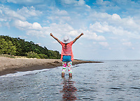 Eight years old girl in water with raised arms. Casual clothing.  Lake Peipsi in Estonia.