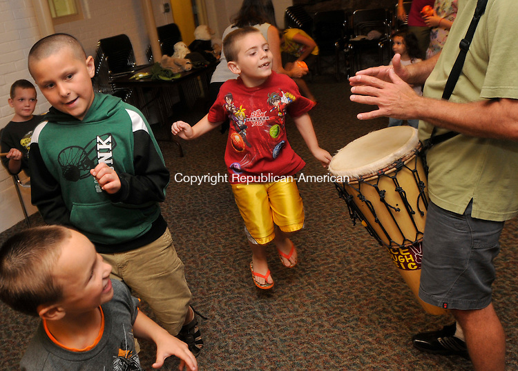 WINSTED, CT-13 JULY 2010-071310IP07- (from left) Xavier Rivera, 6, of Winsted, Brian White, 9, of Winsted and Dominick Zampaglione, 6, of Colebrook, dance to the sounds of a drum played by Craig Norton of Playtivity during &quot;Creature Teachers&quot;, a musical storytelling program at The Beardsley and Memorial Library in Winsted on Tuesday.<br /> Irena Pastorello Republican-American