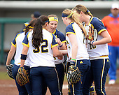 Michigan Wolverines infielder Abby Ramirez (1), shortstop Sierra Romero (32), infielder Caitlin Blanchard (44), utility player Kelsey Susalla (7), pitcher Sara Driesenga (10) meet in between innings during the season opener against the Florida Gators on February 8, 2014 at the USF Softball Stadium in Tampa, Florida.  Florida defeated Michigan 9-4 in extra innings.  (Copyright Mike Janes Photography)