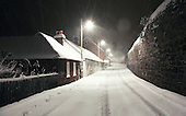 A long exposure shows the snowflakes as long moving streaks.  Snow  falling at night, Petworth, Sussex.