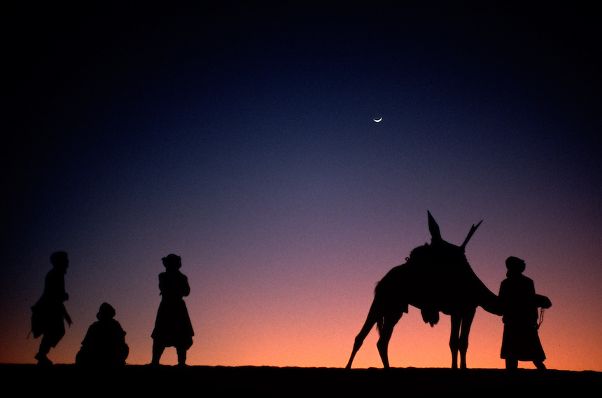 Tuareg riders watch the Festival au Desert music and culture festival in Essakane, Mali, from atop a nearby dune.