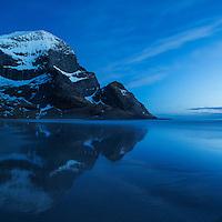 Mountain peaks rise above Bunes beach in spring twilight light, Moskenesoy, Lofoten Islands, Norway