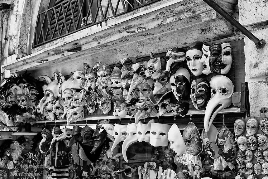 A view of masks on display in a shop in Venice in black and white.