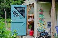 Colorful shed in Yarmouth Community Garden with sign for volunteers, Maine