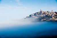 The medieval village of Trevi, towering high above early morning mist in the Spoleto Valley, Umbria, Italy