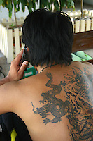 Thai man having a chat on his cellphone, showing his ornate dragon tattoo.  Though temporary tattoos are increasingly popular, the real thing e.g. permanent ones, can be works of art and a form of self-expression.
