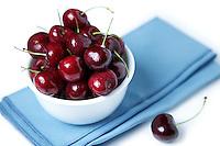 Cherries in white bowl on blue napkin