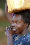 A woman carries water home in the Namokora camp for internally displaced persons. Two decades of war in northern Uganda have left almost two million people displaced, though progress in peace talks in 2006 initiated a small movement to return to home villages.