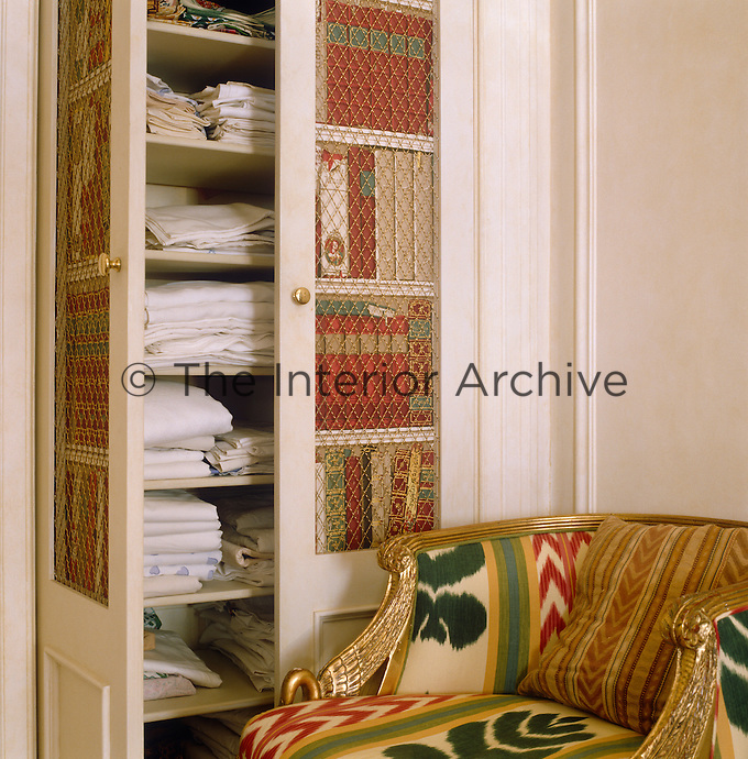 The linen cupboard is disguised as a book case with wallpaper featuring trompe l'oeil books lining the doors