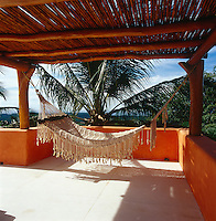 A string hammock slung from the beams of the wooden awning which shades one of several roof terraces, all of which have views over the jungle and ocean beyond