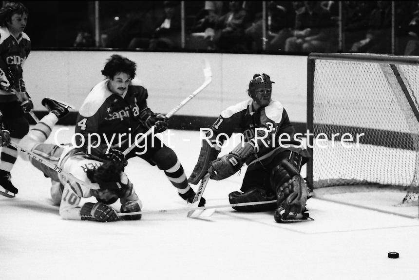 Seals vs Washington Capitols, Bob Paradise blocking Seals Charlie Simmer, goalie Michel Belhumeur. (1975 photo/Ron Riesterer)