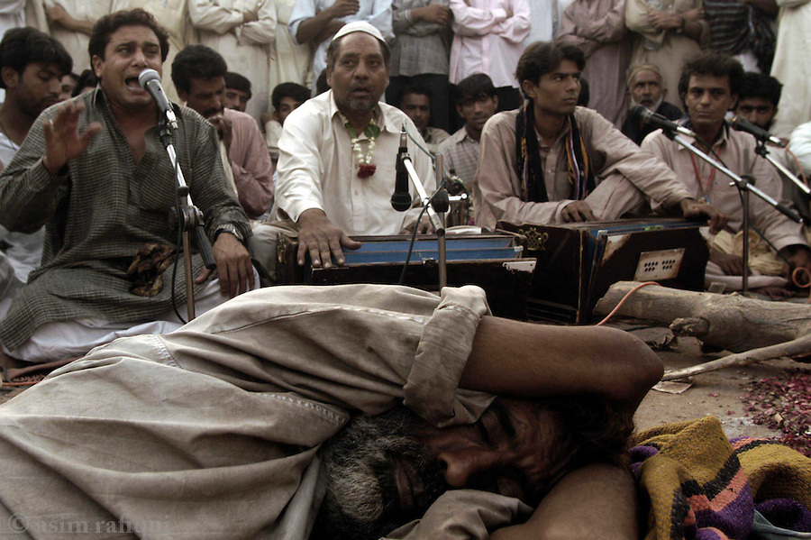bari imam shrine, islamabad, pakistan 2004: musicians sing 'qawwalis' in honor of bari imam and his services to man while a devotee after a night of worship sleeps nearby.  such all night/all day musical sessions are a regular feature of the annual 'urs' and are attended by thousands<br />