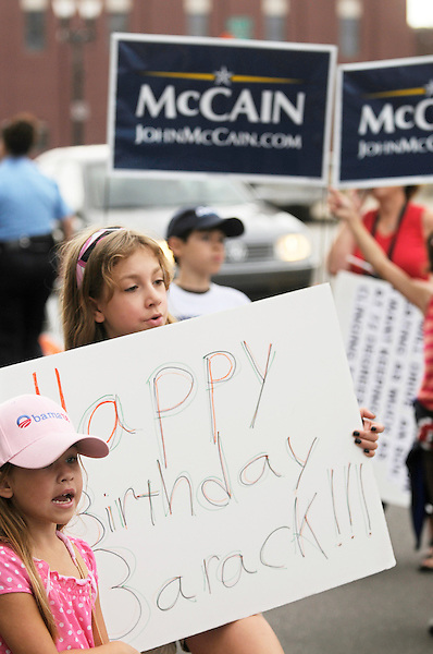Lansing, Michigan: August 4, 2008.A girl holds a sign wishing a happy birthday to presidential candidate and Democrat Barack Obama. Behind her, a boy holds a yard sign supporting John McCain, the Republican presidential candidate. They were demonstrating outside a campaign event featuring Obama. On this date, Obama and McCain were the presumptive nominees of their parties.  ©Christopher Fitzgerald / CandidatePhotos.com