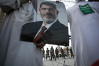 In this Sunday, Jul. 07, 2013 photo, members of the Muslim Brotherhood hold a poster of the ousted president Mohammed Morsi during a rally at the Republican Guard Headquarters in cairo, Egypt. (Photo/Narciso Contreras).