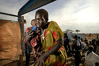 A Dinka woman holds her baby as she boards a truck which will transport them to a barge on the River Nile.  The barge will travel up river, taking displaced Dinka tribespeople back to their homeland of Bor after the civil war.  The resettlement programme is organised by the IOM (International Organisation for Migration).  Tens of thousands of Dinka tribespeople are among the estimated 3.8 million people displaced during the two-decade long conflict between the government and the SPLA (Sudanese People Liberation Army)..