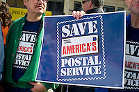 New York Metro Area Postal Union workers and supporters rally near the James Farley Post Office in New York on Saturday, March 17, 2012 to demand that the USPS continue six-day a week mail delivery service. The postal service, which has already cut post office hours as well as other services to meet its budget deficit, is considering elimination of Saturday service which is mandated by Congress. (© Frances M. Roberts)