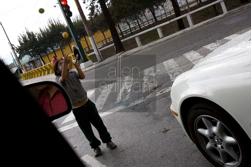 A young girl juggles at an intersection in hopes of a few Quetzales from drivers. Poor Guatemalan children are often sent off to bring in money for families that cannot afford to feed them.