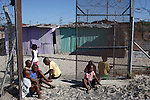 Khayelitsha, South Africa March 5, 2013: Boys wait to register at Amandla EduFootball which was founded by Jakob Schlichtig, Florian Zech outside the field in Khayelitsha a poor township outside Cape Town, South Africa. They use football to initiate, support educational projects for youth in the township. The program keep children busy and it decreases the risk of them joining gang, criminal activity or teenage pregnancy. The crime level has decreased substantially in the area since the program was created in 2006. (Photo by: Per-Anders Pettersson)