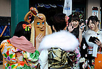Kimono-clad 20-year-old Japanese women have their photos taken by a store selling hot-dogs as they make their way to an event to mark Coming-of-Age Day in Tokyo, Japan on Monday Jan. 11, 2009. Japanese enter adulthood at 20, when they can legally smoke, drink alcohol and vote, though debate is heating up as to whether or not the age should be lowered to 18 in line with many advanced countries. Indeed, the Japanese government plans to lower the voting age to 18 as of mid-2010.   .Photographer: Robert GilhoolyCOMING OF AGE