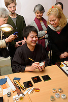 """Maki-e Baisen craftsman Muneaki Shimode gives a demonstration. Kintsugi event, Daiwa Anglo-Japanese Foundation, London, UK, January 24, 2014. Kintsugi literally means """"joining with gold"""": a technique to piece together broken pottery or glass with lacquer, rice-glue and gold."""