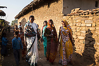 Shanti Adivasi (in white saree), 52, is followed by villagers who are keen to talk to her while she distributes this week's newspapers to her subscribers in Manikpur, Chitrakoot, Uttar Pradesh, India on 4th December 2012.  Shanti used to be a wood gatherer, working with her parents since she was 3, and later carrying up to 100 kg of wood walking 12km from the dry jungle hills to her home to repack the wood which sold for 3 rupees per kg. After learning to read and write in an 8 month welfare course, at age 32, she became a reporter, joining Khabar Lahariya newspaper since its establishment in 2002, and making about 9000 rupees per month, supporting her family of 14 as the sole breadwinner. Photo by Suzanne Lee for Marie Claire France.