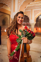Australian violinist Niki Vasilakis poses for a portrait with her bouquet of flowers after her solo violin concert played to a prominent audience, including the Jaipur Royal Family, and other VIPs at the OzFest Gala Dinner in the Jaipur City Palace, in Rajasthan, India on 10 January 2013. Photo by Suzanne Lee