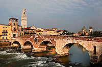 General view of Il Ponte Pietra, 100 BC, across the Adige River, with its Torre di Guardia (Watch Tower), 13th century, Verona, Italy. The bell tower of the Cathedral (Duomo) and, on the right, in the distance, the church of San Giorgio in Braida can be seen. The Via Postumia from Genua to the Brenner Pass crossed the Roman Ponte Pietra, or 'Stone Bridge', once known as the Pons Marmoreus. Its right hand arch was rebuilt in 1298 by Alberto I della Scala, and during the 2nd World War retreating German troops blew up 4 arches of the bridge,  which were rebuilt using original materials in 1957. Picture by Manuel Cohen.