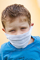 Boy with medical mask in front of yellow background