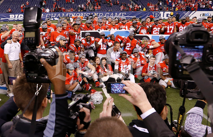 The Ohio State football team poses for pictures following the 59-0 win over Wisconsin in the Big Ten Championship game at Lucas Oil Stadium in Indianapolis on Dec. 6, 2014. (Adam Cairns / The Columbus Dispatch)