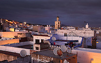 Rooftops of the medina or old town and the 18th century minaret of the Zaouiat Sidi ali Benraisoun or Octagonal Mosque in Tetouan in the evening, on the slopes of Jbel Dersa in the Rif Mountains of Northern Morocco. Tetouan was of particular importance in the Islamic period from the 8th century, when it served as the main point of contact between Morocco and Andalusia. After the Reconquest, the town was rebuilt by Andalusian refugees who had been expelled by the Spanish. The medina of Tetouan dates to the 16th century and was declared a UNESCO World Heritage Site in 1997. Picture by Manuel Cohen