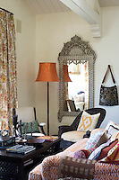 A large mother of pearl and ivory inlaid mirror hangs on the wall of the sitting room