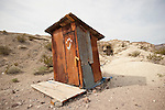 Corrugated rusty outhouse with painted crescent moon and four stars, Dublin Gulch near Shoshone, Calif.
