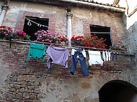 Colorful clothes hang over a balcony to dry in the Tuscan sun in the small medieval village of San Quirico d'Orcia, Italy - June 20, 2005.  San Quirico d'Orcia is an ancient walled city on the northern edge of the Val d'Orcia in southern Tuscany.