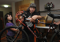 NWA Democrat-Gazette/FLIP PUTTHOFF<br /> Robbie Rheam (cq), 9, helps Gloria Eby put a tag Saturday August 8 2015 on a bike indicating it has been repaired.