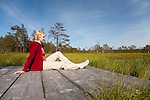 Young Woman Sitting on Wooden Boardwalk in Viru Bog, Lääne-Viru County, Estonia