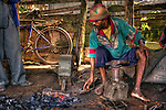In central Madagascar, a metal smith repairs and makes tools at a market.