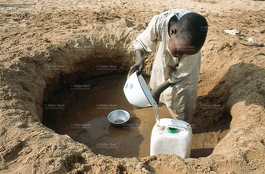 Sudan. West Darfur. Kerenek. A young boy fetches water in the bed of the dry river (also called wadi) and fill it in a plastic water container. © 2004 Didier Ruef