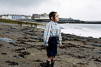 An Hasidic boy look out to sea from the beach in Aberystwyth.