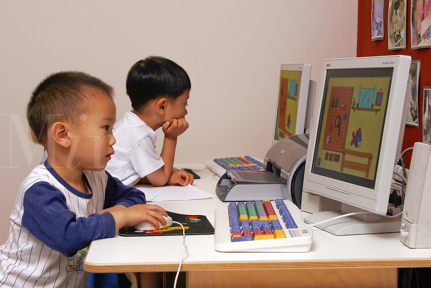 Preschool students playing educational games at the computer.