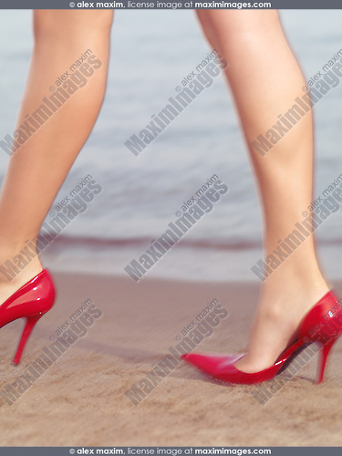 Woman in sexy red high heel shoes walking by sand on the beach