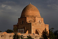 General view of Rukhabad Mausoleum, 14th century, Samarkand, Uzbekistan, pictured on July 18, 2010, in the afternoon beneath a stormy sky. The Rukhabad Mausoleum (Abode of the Spirit) was built by Timur over the grave of the mystic Sheikh Burhan al-Din Sagarji. The cubic building is topped with a dome based on an octahedron and mausoleum has three entrances. The simple interior walls are covered with alabaster plasterwork with one glazed tile band. A  19th century carved wooden door leads to the tomb. Samarkand, a city on the Silk Road, founded as Afrosiab in the 7th century BC, is a meeting point for the world's cultures. Its most important development was in the Timurid period, 14th to 15th centuries. Picture by Manuel Cohen.