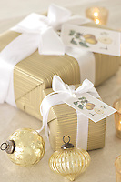 A close up of Christmas parcels tied with ribbon and gold baubles