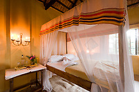 Mosquito nets draped over the bed at the Ndali Lodge, Uganda, East Africa