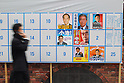 March 25, 2011, Tokyo, Japan - A man walks past posters of candidates for the Tokyo gubernatorial elections displayed at Shimbashi district on Friday, March 25, 2011. The natiowide local elections campaign officially kicked off in 12 prefectures ahead of voting on April 10, while Iwate Prefecture has put off its race in the aftermath of the March 11 catastrophic earthquake. (Photo by YUTAKA/AFLO) [1040] -ty-.