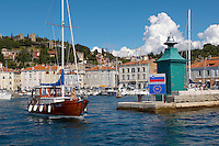 Harour entance with people relaxing and fishing off the harbour wall with a sailing boat. Piran , Slovenia