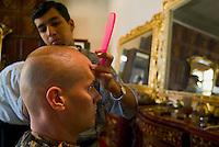 """Baghdad, Iraq, June 5, 2003.US Captain Polpek from the 422nd Civil Affairs gets a $1 hair cut at Saddam's Palace salon; at this stage of the procedings, he just said: """"a little shorter on the top, please""""...."""