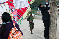 A Bolivian Navy soldier holds an RPG as locals hang up banners to mourn the day they lost their ocean to Chile in the War of the Pacific. Bolivia lost what is now northern Chile in a war over nitrates leaving Bolivia without access to the ocean.