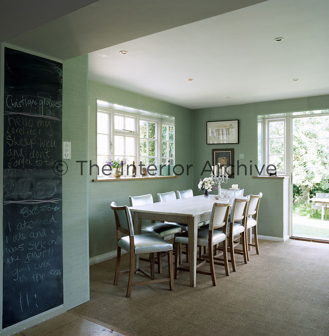 In the dining room the walls are covered in a textured sage-green paper and the chairs are upholstered in stunning silver leather