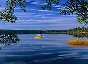 Reflection of yellow sailboat in Lake Massabesic in Auburn, New Hampshire USA.